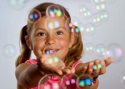 Dzieczynka łapie bańki mydlane